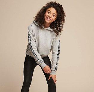 A smiling girl wearing a grey hoodie with black leggings.
