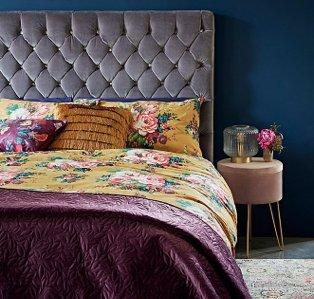 A double bed with a yellow floral bedspread, fringe accent cushions and a plum throw next to a bedside table with a glass lamp and a vase of pink flowers.