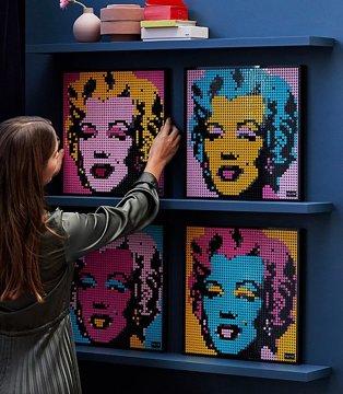 A woman placing four LEGO Art Andy Warhol portraits on a wall shelf.