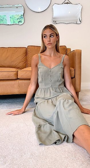 Woman sitting on the floor against a sofa wearing a khaki tiered midi dress