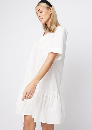 Woman wearing a white tiered smock dress with black headband