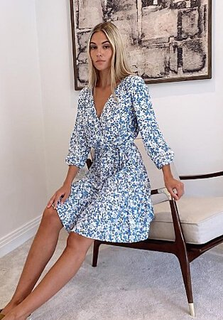 Woman leaning against an armchair wearing a blue floral mock wrap top tiered dress