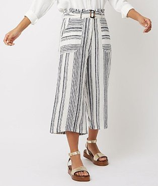 Woman in white shirt tucked into monochrome patterned cropped wide leg palazzo trousers with gold-tone two-strap sandals