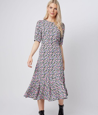 Woman in pink floral frill hem tiered midi dress and black ankle boots