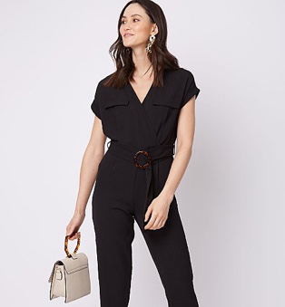 Woman wearing a black belted utility jumpsuit and holding a cream bag with a tortoiseshell handle