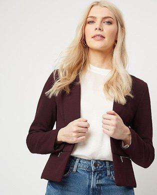 Woman in a burgundy blazer over a cream top and jeans