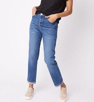 Woman in black top, mid wash denim high rise straight jeans and pink trainers