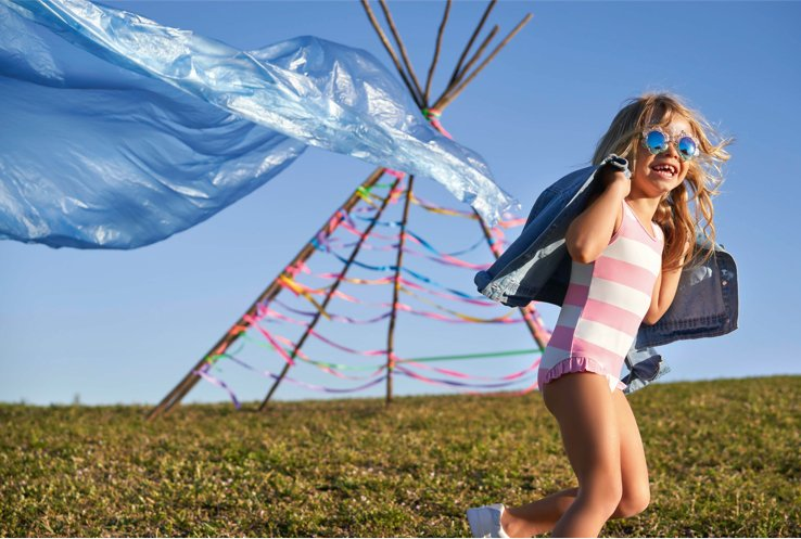 Young girl wearing pink and white striped swimsuit with denim jacket and pink sunglasses running around a tee-pee in a field
