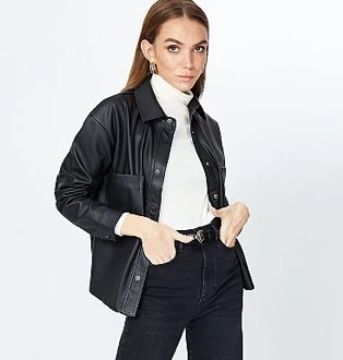Brunette woman poses wearing white roll neck top, black leather-effect shacket and black belted jeans.
