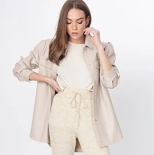 Brunette woman poses with hand on hip and hand raised to side of face wearing beige faux-leather longline shacket over white t-shirt and stone drawstring waistband joggers.