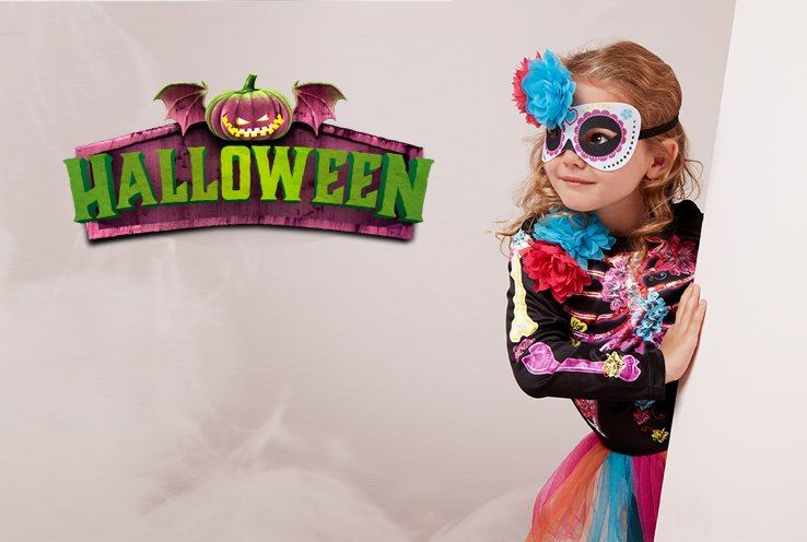 Girl poses on white wall wearing floral skeleton fancy dress costume