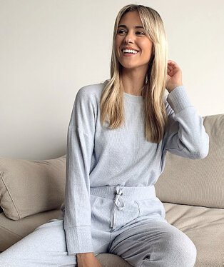 Woman poses smiling sitting on sofa wearing grey top and matching trousers.