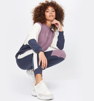 Woman poses crouched down wearing grey, purple and white hoodie and trousers.
