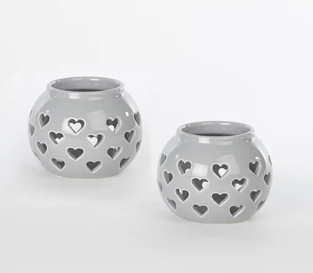 Two grey candle holders with heart shape cut outs