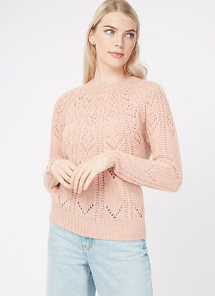 Woman wearing a pale pink pointelle chevron jumper and light wash jeans