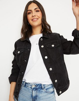 Woman wearing a black wash denim jacket over a white t-shirt and light wash jeans