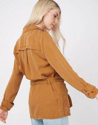 Woman facing backwards wearing a tan belted woven utility jacket