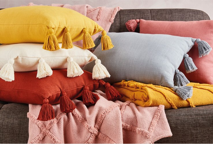 A selection of cushions with tassels in yellow, white, pink and grey