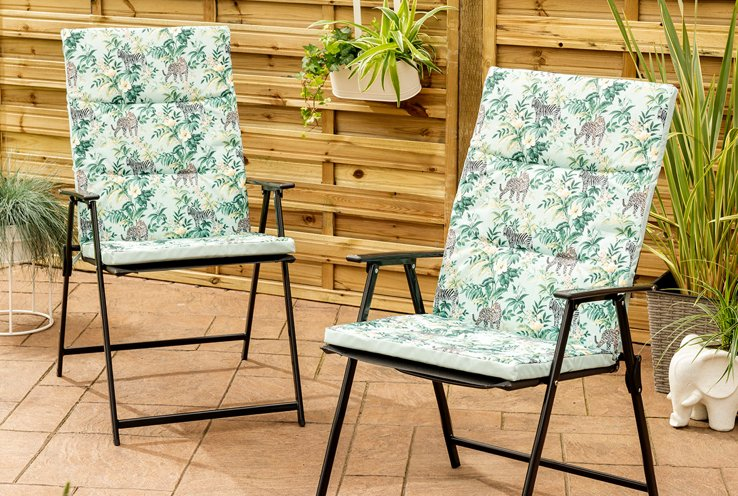 Two seats with safari miami outdoor seat cushions on patio with potted plants and hanging baskets in the background.