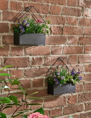 Brick wall with two black house-shaped wall planters containing pink and purple flowers.