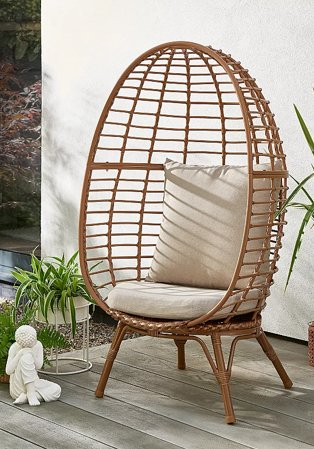 Novaro garden egg chair with cream seat cushion on patio surrounded by artificial plants and a cream buddha ornament.