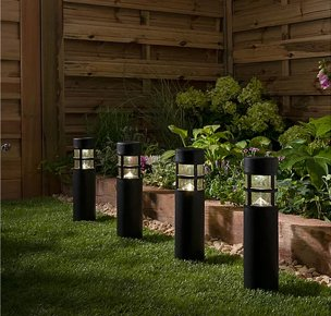 Fenced garden with a line of 4 black outdoor white LED lighthouse pillars placed on grass with an array of plants and greenery in the background.