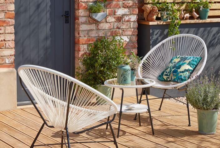 White Camden outdoor bistro 3 piece set on a garden patio with plants around it