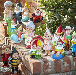 A large collection of garden gnomes on a garden wall, including one dressed in a bumblebee costume, one riding a dinosaur and more