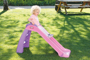 Girl going down a small pink slide in a garden