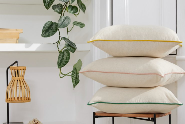 Three natural cushions with yellow, pink and green piping stacked on a wooden chair with white shelves and artificial plant in the background.