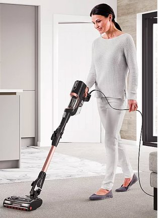Woman vacuums grey carpet wearing grey lounge top and bottoms and dark grey ballet shoes.