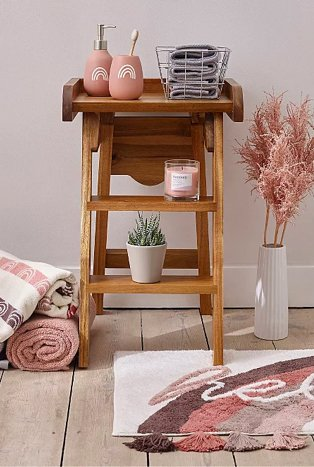 Wooden table topped with pink rainbow dispenser and tumbler set, grey storage basket, pink candle and artificial plant surrounded by pink and cream rolled towels, pink artificial plant in white vase and cream, brown and pink hello slogan bath mat.