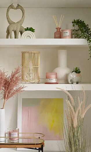 White shelves with giraffe ornament, rainbow artificial plant, elephant artificial plant, pink candle and diffuser set, wicker lamp, pink artificial plant in white vase, green and pink framed print, gold-tone wire tray and pink candle.