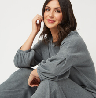Woman sitting wearing a grey sweatshirt and matching joggers outfit