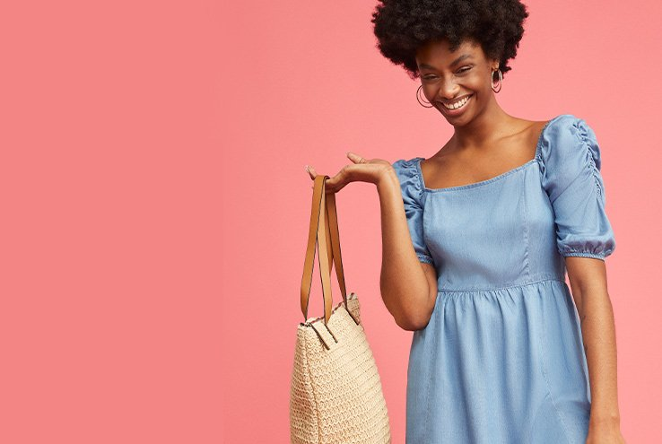 Woman smiles wearing blue puff sleeve denim dress holding natural woven straw tote bag.