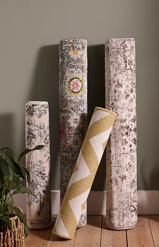 4 assorted abstract printed rugs stood upright on wooden floor against a grey wall.