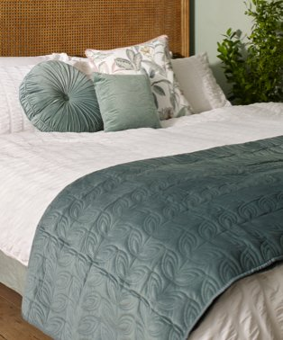 Double bed with wooden headboard features white bedding set, green pinsonic throw, green pleated pinwheel cushion, green pinsonic cushion and cream leafy cushion with large artificial plant in corner of room.