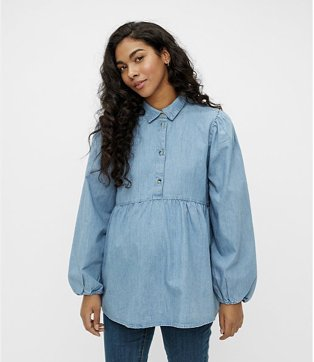 Woman poses smiling wearing maternity blue denim shirt over blue jeans.