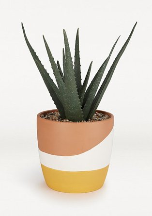 Artificial aloe vera plant in orange and yellow patterend pot.