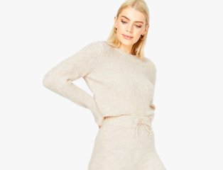 Woman poses with hands on hips wearing nude matching cardigan and trousers co-ord set.