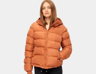 Woman poses wearing PIECES burnt orange puffer jacket and black jeans.