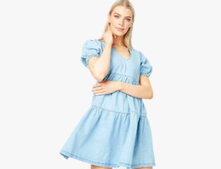 Woman poses with arm across body wearing light blue denim tiered dress.