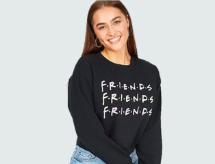 Woman poses smiling wearing black Friends TV show cropped logo sweatshirt and mid-wash blue jeans.