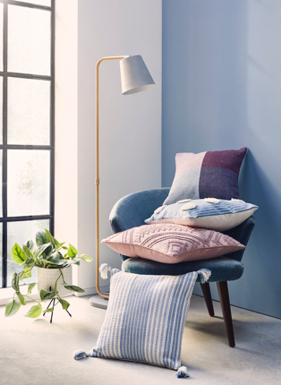 An assortment of cushions on a blue chair next to a floor lamp and plant