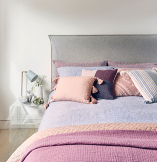 A double bed with blue printed bedding, a pink and purple throw, an assortment of cushions and a side table with a lamp and other accessories