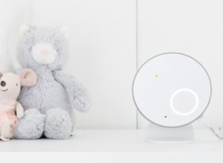 Angelcare white baby movement monitor with grey bear and pink mouse on the right