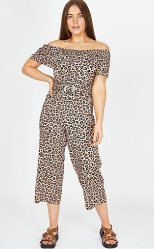 Woman poses with hand on hip wearing leopard print belted Bardot jumpsuit and brown studded sandals.