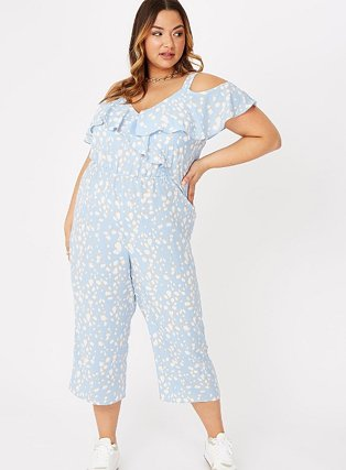 Woman poses with one hand on hip wearing blue abstract spot print cold shoulder jumpsuit and white trainers.