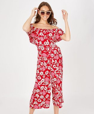 Woman poses smiling with hands raised to head wearing red floral cold shoulder jumpsuit and nude oversized sunglasses.