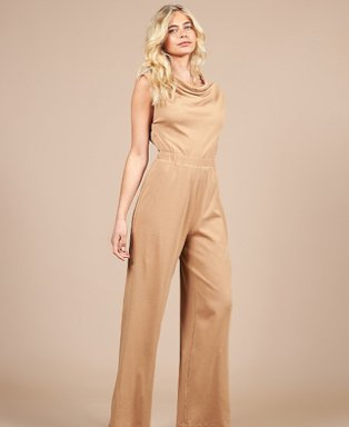 Woman poses wearing Girls On Film camel jersey jumpsuit.
